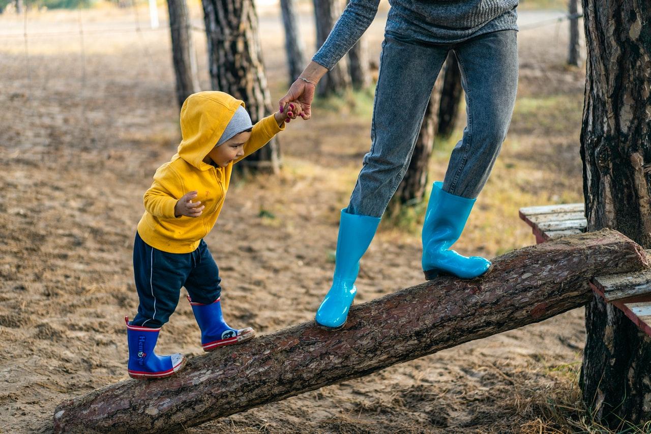 Lille dreng og forældre leger på legeplads