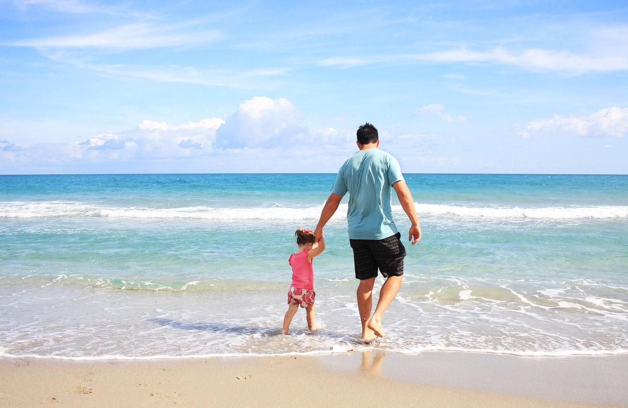 Far og datter går en tur på en strand